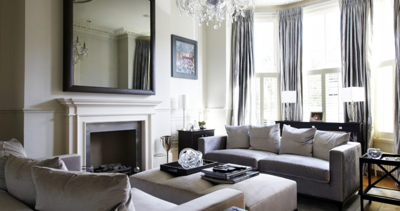 designer-living-room-furniture-carpet-white-sofa-cushions-chair-pouf-table-mirror-frame-ceiling-lights-chandelier-vase-with-plants-window